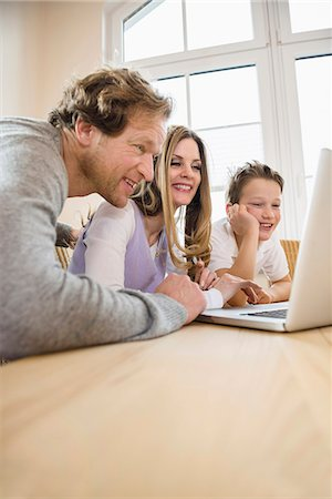 Family using laptop at home Stock Photo - Premium Royalty-Free, Code: 6121-07809871
