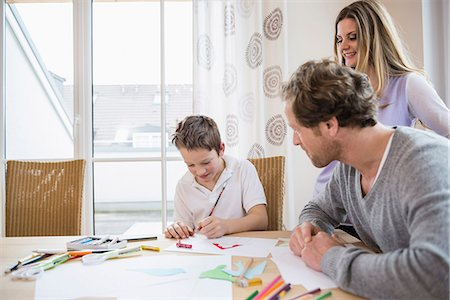 elementary age - Boy drawing a picture with parents at table Stock Photo - Premium Royalty-Free, Code: 6121-07809880