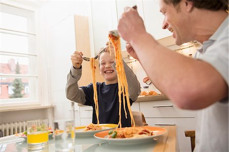 family table eating together - Father and son eating spaghetti in kitchen Stock Photo - Premium Royalty-Free, Code: 6121-07809802