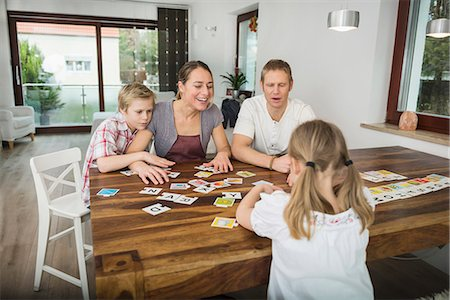 Family at living room playing parlor game together Stock Photo - Premium Royalty-Free, Code: 6121-07809813