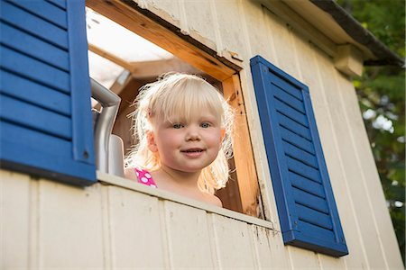 Smiling little girl looking out of tree house Stock Photo - Premium Royalty-Free, Code: 6121-07809833