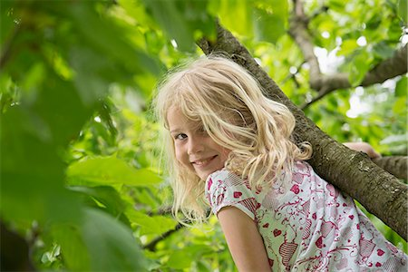 Young blonde girl in garden climbing tree Stock Photo - Premium Royalty-Free, Code: 6121-07809951