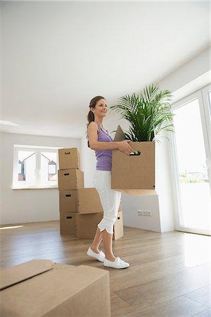 Woman carrying boxes new home moving in Stock Photo - Premium Royalty-Free, Code: 6121-07809980