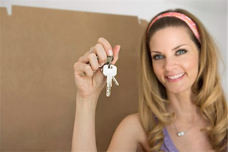 Portrait woman holding house keys new apartment Stock Photo - Premium Royalty-Free, Code: 6121-07809984