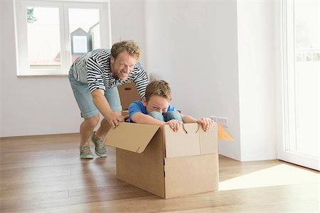 pushing - Father son new apartment playing cardboard box Stock Photo - Premium Royalty-Free, Code: 6121-07809995