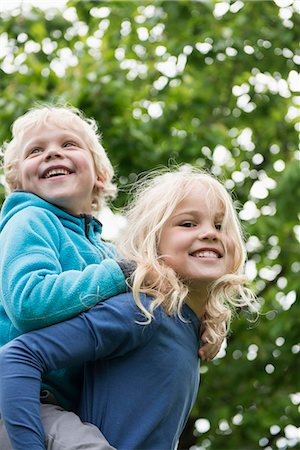 Young blonde girl carrying brother piggyback Stock Photo - Premium Royalty-Free, Code: 6121-07809923