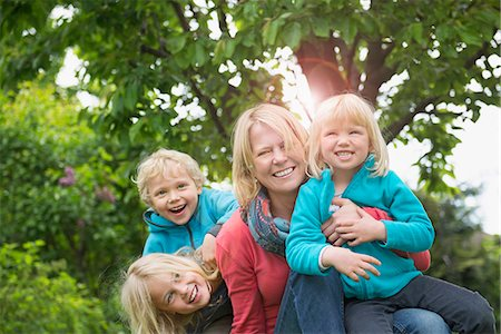 Mother playing with three young kids in garden Stock Photo - Premium Royalty-Free, Code: 6121-07809937