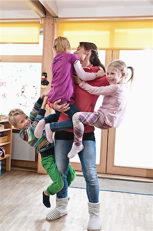 Female educator rampaging with three kids in kindergarten Stock Photo - Premium Royalty-Free, Code: 6121-07810093