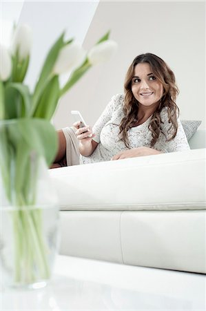 Portrait of smiling young woman with smartphone lying on couch at home Stock Photo - Premium Royalty-Free, Code: 6121-07810163