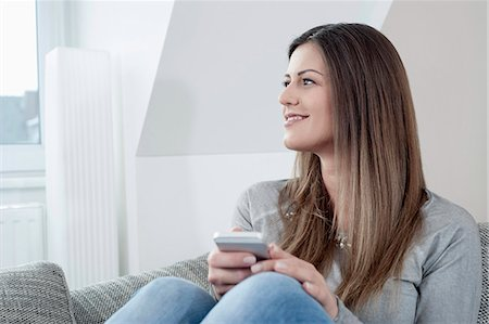 Portrait of smiling young woman with smartphone sitting on couch at home Stock Photo - Premium Royalty-Free, Code: 6121-07810166