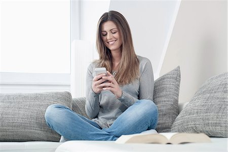 Portrait of smiling young woman with smartphone sitting on couch at home Stock Photo - Premium Royalty-Free, Code: 6121-07810170