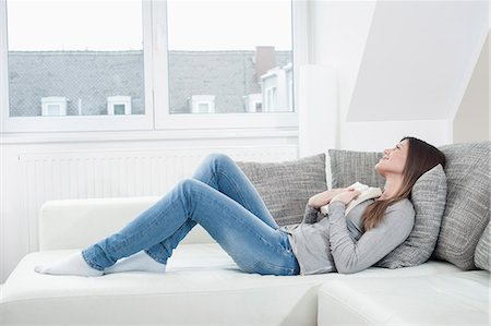 Young woman with opened book lying on couch at home Stock Photo - Premium Royalty-Free, Code: 6121-07810177