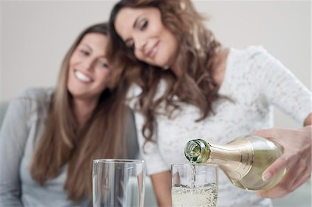 Young woman pouring champage into glasses while her female friend watching Stock Photo - Premium Royalty-Free, Code: 6121-07810182