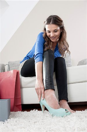 Portrait of young woman sitting on couch at home trying on new high heels Stock Photo - Premium Royalty-Free, Code: 6121-07810194