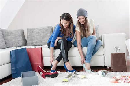 Two young female friends sitting side by side on couch at home trying on high heels Stock Photo - Premium Royalty-Free, Code: 6121-07810195