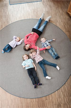 Female educator and four kids relaxing on ground in kindergarten, elevated view Stock Photo - Premium Royalty-Free, Code: 6121-07810107