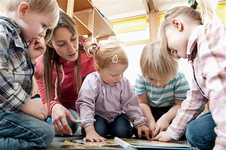 Female educator and four kids looking at picture book Stock Photo - Premium Royalty-Free, Code: 6121-07810105