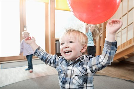 Kids playing with red balloons in kindergarten Stock Photo - Premium Royalty-Free, Code: 6121-07810109