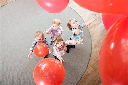 red - Four kids playing with red balloons in kindergarten, elevated view Stock Photo - Premium Royalty-Free, Code: 6121-07810110