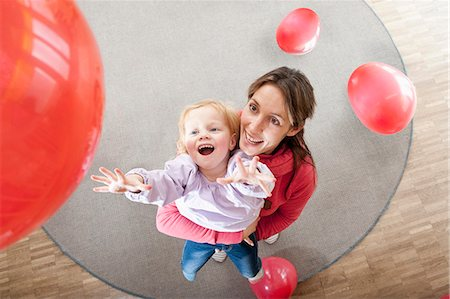 Female educator and little girl playing with red balloons in kindergarten Stock Photo - Premium Royalty-Free, Code: 6121-07810111