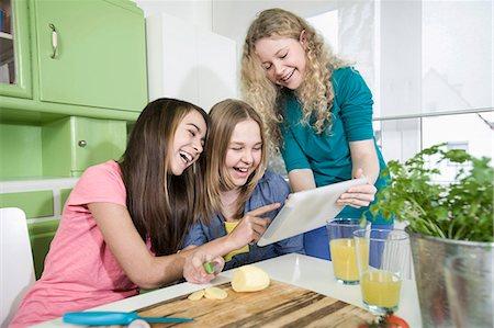 Girls in kitchen with digital tablet, preparing vegetables Stock Photo - Premium Royalty-Free, Code: 6121-07810133