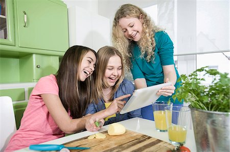 Girls in kitchen with digital tablet, preparing vegetables Stock Photo - Premium Royalty-Free, Code: 6121-07810133