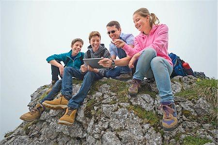 Father teenage kids sitting on rocks using iPad Stock Photo - Premium Royalty-Free, Code: 6121-07810257