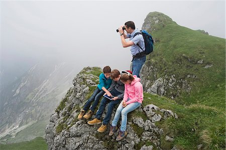 Father teenage kids in mountains iPad computer Stock Photo - Premium Royalty-Free, Code: 6121-07810255