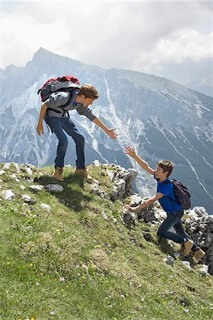 Teenage boys helping friend climbing in mountains Stock Photo - Premium Royalty-Free, Code: 6121-07810267