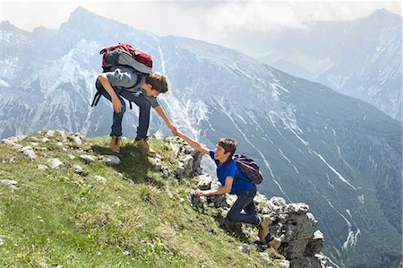 Teenage boys helping friend climbing in mountains Stock Photo - Premium Royalty-Free, Code: 6121-07810268