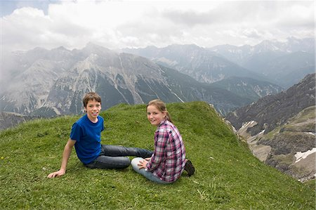 Young girl and boy sitting on grass Alps Stock Photo - Premium Royalty-Free, Code: 6121-07810273