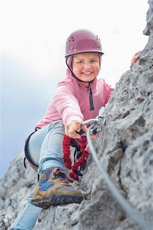 Teenage girl climbing attaching carabiner to rope Stock Photo - Premium Royalty-Free, Code: 6121-07810280