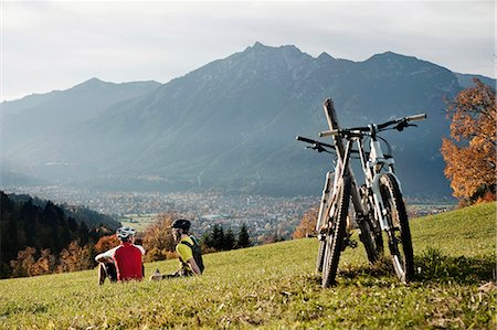 Two Mountainbikers resting on grass enjoying view Stock Photo - Premium Royalty-Free, Code: 6121-07810295