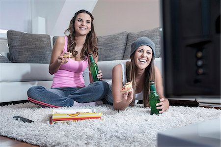 Two female friends side by side on carpet at home watching television Stock Photo - Premium Royalty-Free, Code: 6121-07810202