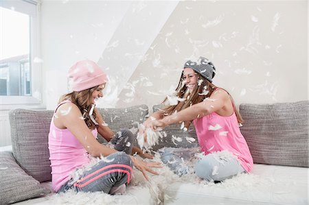 funny looking people - Two female friends sitting on couch at home having pillow fight Stock Photo - Premium Royalty-Free, Code: 6121-07810206