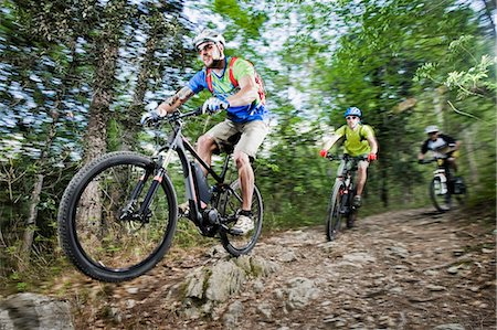 Three Mountainbikers stunt racing forest track Stock Photo - Premium Royalty-Free, Code: 6121-07810366