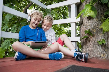 Young boys tree-house tablet computer headphones Stock Photo - Premium Royalty-Free, Code: 6121-07810385