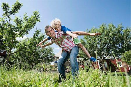 Son boy father piggyback garden playing fun Stock Photo - Premium Royalty-Free, Code: 6121-07810393