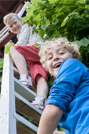 Young boys friends climbing ladder tree-house Stock Photo - Premium Royalty-Free, Code: 6121-07810391