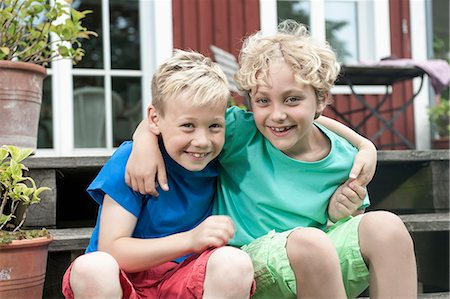 Friends young boys sitting steps house smiling Stock Photo - Premium Royalty-Free, Code: 6121-07810396