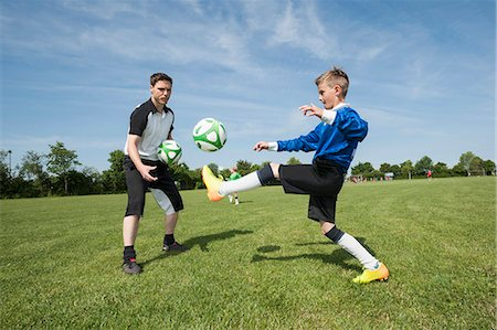 practise - Soccer trainer teaching young player helping Stock Photo - Premium Royalty-Free, Code: 6121-07810303