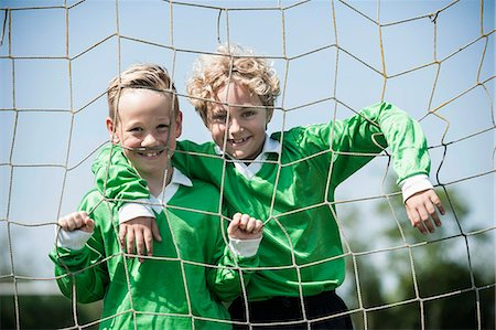 Two young football players posing in goal Stock Photo - Premium Royalty-Free, Code: 6121-07810305
