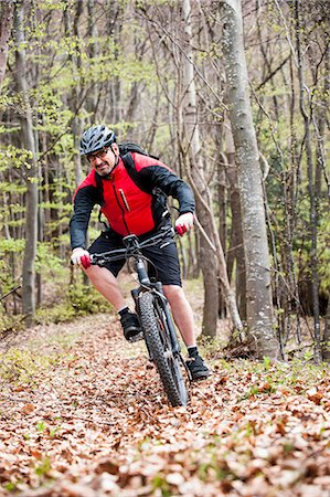 Man racing autumn forest electric mountainbike Stock Photo - Premium Royalty-Free, Code: 6121-07810322