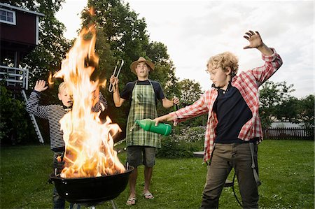 Boy pouring methylated spirit on barbecue fire Stock Photo - Premium Royalty-Free, Code: 6121-07810440