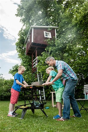 Working building father sons garden tree-house Stock Photo - Premium Royalty-Free, Code: 6121-07810400