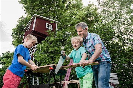Boy sawing wood building father helping Stock Photo - Premium Royalty-Free, Code: 6121-07810401