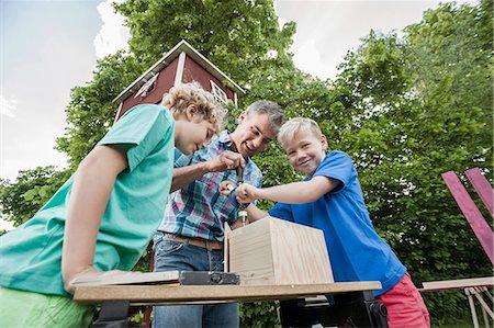 drilling - Boys father constructing birdhouse garden wood Stock Photo - Premium Royalty-Free, Code: 6121-07810407