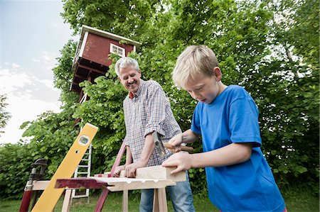 Grandfather grandson working together building Stock Photo - Premium Royalty-Free, Code: 6121-07810410