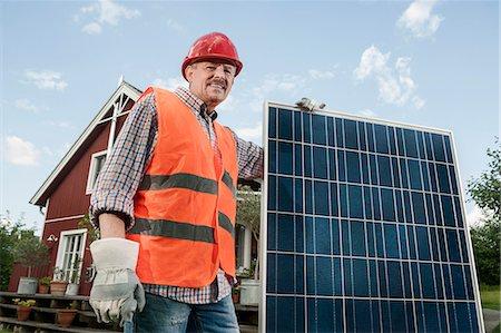 solar power - Close up portrait man holding solar panel Stock Photo - Premium Royalty-Free, Code: 6121-07810428