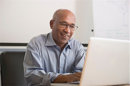 African businessman office desk laptop computer Stock Photo - Premium Royalty-Free, Code: 6121-07970041